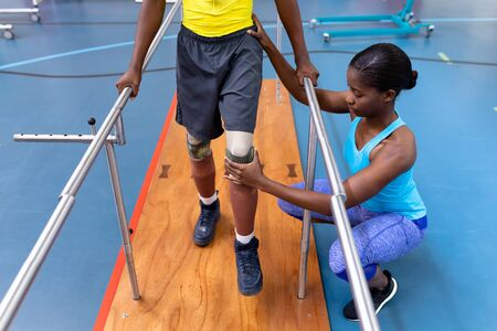 High angle view of African-american physiotherapist assisting disabled African-american man walk with parallel bars in sports center. Sports Rehab Centre with physiotherapists and patients working together towards healing Archivio Fotografico