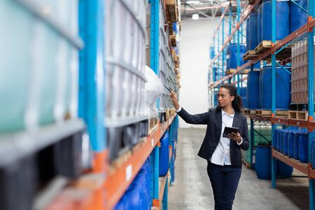 African American female manager checking stocks while using digital tablet in warehouse. This is a freight transportation and distribution warehouse. Industrial and industrial workers concept