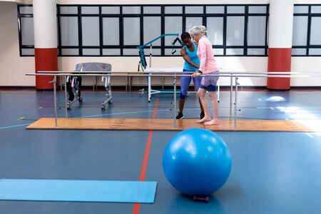 Side view of African-american female physiotherapist helping disabled Caucasian senior woman walk with parallel bars in sports center. Sports Rehab Centre with physiotherapists and patients working together towards healing
