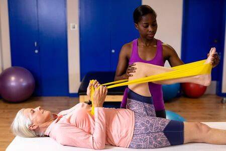 Female physiotherapist assisting woman to exercise with resistance band in sports center. Sports Rehab Centre with physiotherapists and patients working together towards healing Archivio Fotografico