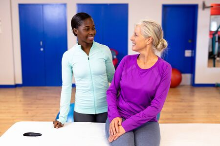 Front view of female physiotherapist talking with active senior woman in sports center. Sports Rehab Centre with physiotherapists and patients working together towards healing Archivio Fotografico - 128270890