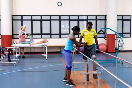High angle view of African-american Female physiotherapist helping disabled African-american man walk with parallel bars in sports center. Sports Rehab Centre with physiotherapists and patients working together towards healing Archivio Fotografico - 128270887