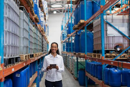 African American female manager using digital tablet in warehouse. This is a freight transportation and distribution warehouse. Industrial and industrial workers concept Archivio Fotografico - 128270891