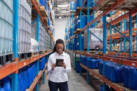 African American female manager using digital tablet in warehouse. This is a freight transportation and distribution warehouse. Industrial and industrial workers concept Archivio Fotografico - 128270894