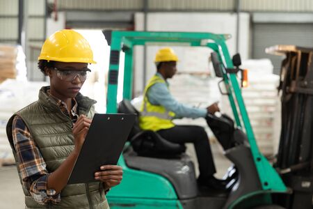 Front view of female worker writing on clipboard in warehouse. This is a freight transportation and distribution warehouse. Industrial and industrial workers concept Archivio Fotografico - 128270999