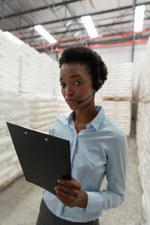 Close-up of female manager with headset and clipboard looking at camera in warehouse. This is a freight transportation and distribution warehouse. Industrial and industrial workers concept