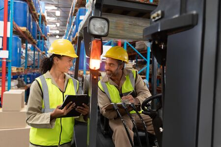 Multi-ethnic male and female staff discussing over clipboard in warehouse. This is a freight transportation and distribution warehouse. Industrial and industrial workers concept