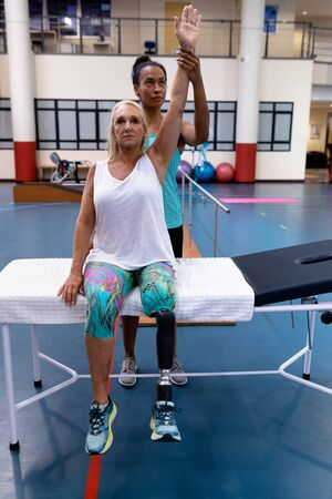 Front view of African-american Female trainer assisting disabled Caucasian active senior woman to exercise in sports center. Sports Rehab Centre with physiotherapists and patients working together towards healing