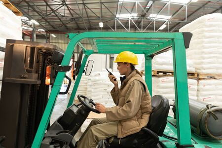 Side view of female worker talking on walkie-talkie while driving forklift in warehouse. This is a freight transportation and distribution warehouse. Industrial and industrial workers concept Reklamní fotografie