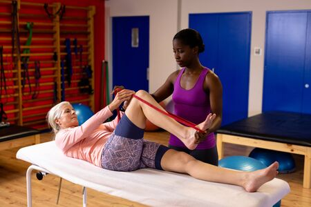 Female physiotherapist assisting woman to exercise with resistance band in sports center. Sports Rehab Centre with physiotherapists and patients working together towards healing Reklamní fotografie