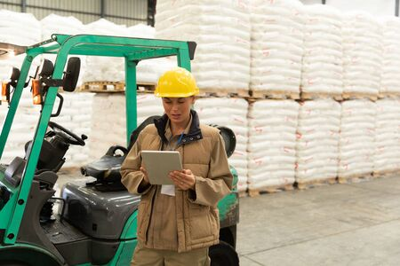 Front view of female worker using digital tablet in warehouse. This is a freight transportation and distribution warehouse. Industrial and industrial workers concept Stok Fotoğraf