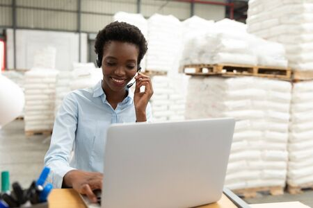 Happy female manager talking on headset while using laptop at desk in warehouse. This is a freight transportation and distribution warehouse. Industrial and industrial workers concept Archivio Fotografico - 128271010