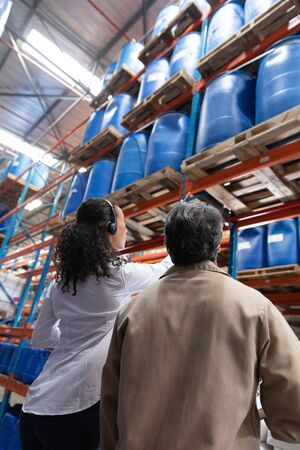 Low angle view of female manager and male staff interacting with each other while checking stocks in warehouse. This is a freight transportation and distribution warehouse. Industrial and industrial workers concept