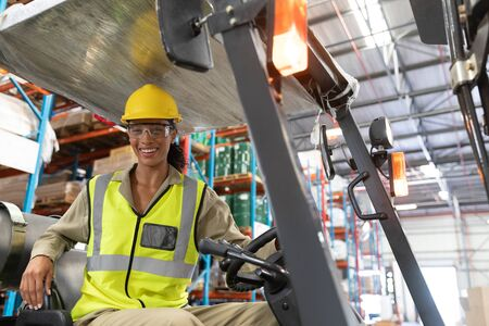 Portrait of female staff driving forklift in warehouse. This is a freight transportation and distribution warehouse. Industrial and industrial workers concept Archivio Fotografico - 128271036