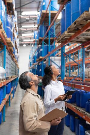 Female manager and male staff checking stocks together in warehouse. This is a freight transportation and distribution warehouse. Industrial and industrial workers concept Archivio Fotografico - 128271035
