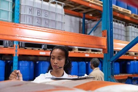 Female manager talking on headset while checking stocks in warehouse. This is a freight transportation and distribution warehouse. Industrial and industrial workers concept Stok Fotoğraf