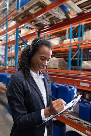 African American female manager writing on clipboard while talking on headset in warehouse. This is a freight transportation and distribution warehouse. Industrial and industrial workers concept