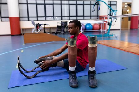 Side view of African-american disabled man exercising on exercise mat in sports center. Sports Rehab Centre with physiotherapists and patients working together towards healing