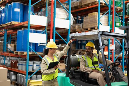 Happy male and female staff interacting with each other in warehouse. This is a freight transportation and distribution warehouse. Industrial and industrial workers concept Archivio Fotografico - 128271070