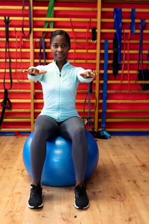Front view of woman exercising with exercise ball in sports center. Sports Rehab Centre with physiotherapists and patients working together towards healing