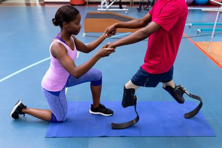 Side view of African-american physiotherapist helping disabled African-american man walk with prosthetic leg in sports center. Sports Rehab Centre with physiotherapists and patients working together towards healing Stok Fotoğraf