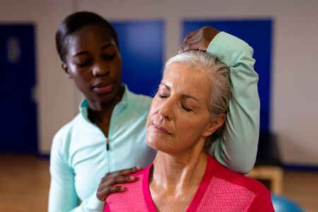 Close-up of female physiotherapist giving neck massage to active senior woman in sports center. Sports Rehab Centre with physiotherapists and patients working together towards healing Stok Fotoğraf
