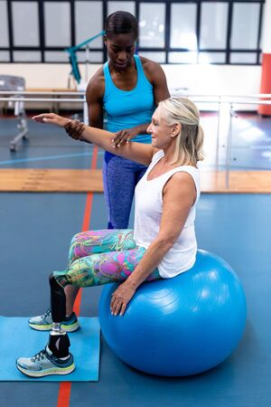 Front view of African-american Female trainer assisting disabled Caucasian senior woman in sports center. Sports Rehab Centre with physiotherapists and patients working together towards healing Reklamní fotografie