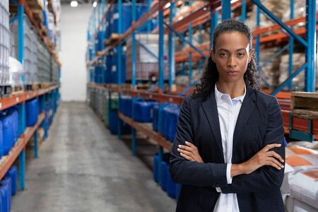 Portrait of female manager standing with arms crossed in warehouse. This is a freight transportation and distribution warehouse. Industrial and industrial workers concept Reklamní fotografie