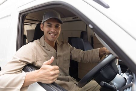 Front view of delivery man showing thumbs up while sitting in front seat of car outside the warehouse. This is a freight transportation and distribution warehouse. Industrial and industrial workers concept