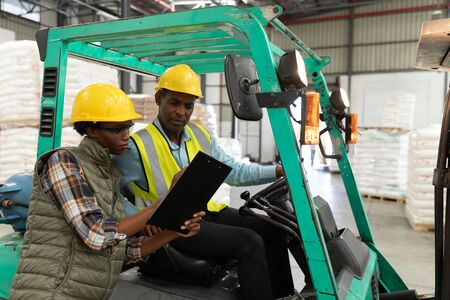 Side view of male and female worker discussing over clipboard in warehouse. This is a freight transportation and distribution warehouse. Industrial and industrial workers concept