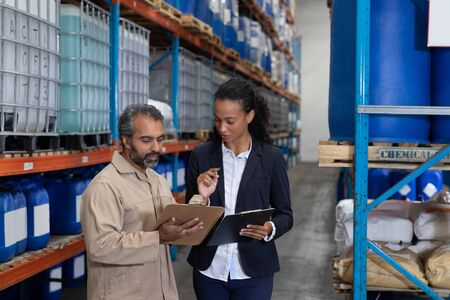 Front view of female manager and male worker discussing over clipboard in warehouse. This is a freight transportation and distribution warehouse. Industrial and industrial workers concept Reklamní fotografie