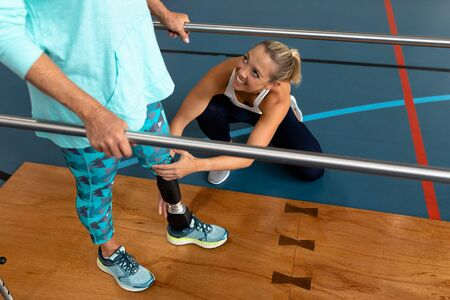 High angle view of female physiotherapist helping disabled senior woman walk with parallel bars in sports center. Sports Rehab Centre with physiotherapists and patients working together towards healing Reklamní fotografie