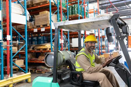 Portrait of male staff writing on clipboard while sitting on forklift in warehouse. This is a freight transportation and distribution warehouse. Industrial and industrial workers concept