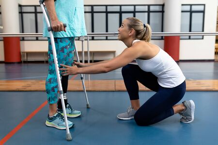 Side view of female physiotherapist assisting disabled senior woman walk with elbow crutches in sports center. Sports Rehab Centre with physiotherapists and patients working together towards healing