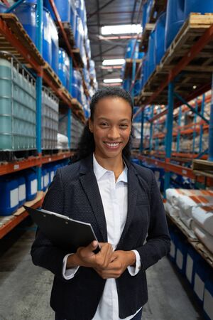 Close-up of female manager holding clipboard in warehouse. This is a freight transportation and distribution warehouse. Industrial and industrial workers concept