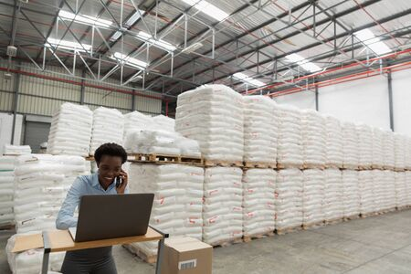 Front view of female manager talking on mobile phone while using laptop at desk in warehouse. This is a freight transportation and distribution warehouse. Industrial and industrial workers concept