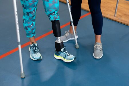 Low section of female physiotherapist assisting disabled senior woman walk with elbow crutches in sports center. Sports Rehab Centre with physiotherapists and patients working together towards healing Reklamní fotografie