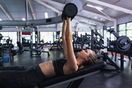 Side view of Caucasian woman exercising with dumbbell in fitness center. Bright modern gym with fit healthy people working out and training
