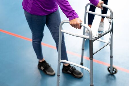 Low section of Disabled senior woman walking with walker in sports center. Sports Rehab Centre with physiotherapists and patients working together towards healing Reklamní fotografie