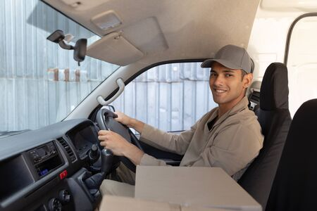 Side view of delivery man with cardboard boxes sitting in front seat of car outside the warehouse. This is a freight transportation and distribution warehouse. Industrial and industrial workers concept