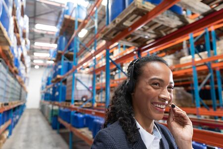 Close-up of female manager talking on headset in warehouse. This is a freight transportation and distribution warehouse. Industrial and industrial workers concept Stok Fotoğraf