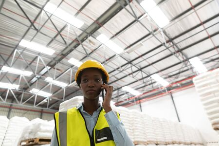 Low angle view of female worker talking on mobile phone in warehouse. This is a freight transportation and distribution warehouse. Industrial and industrial workers concept Archivio Fotografico - 128271053
