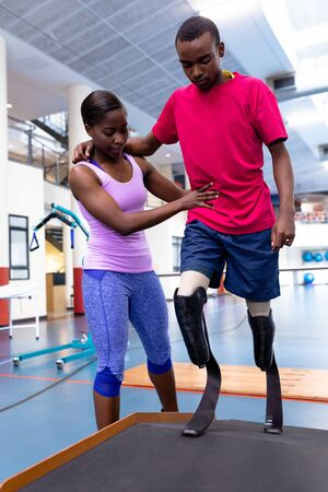 Front view of African-american physiotherapist helping disabled African-american man walk with prosthetic leg on ramp in sports center. Sports Rehab Centre with physiotherapists and patients working together towards healing Reklamní fotografie