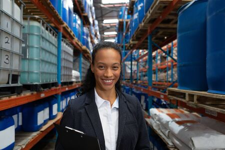 Portrait of female manager standing with clipboard in warehouse. This is a freight transportation and distribution warehouse. Industrial and industrial workers concept Archivio Fotografico - 128271020