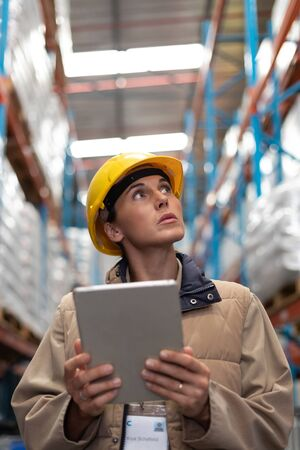 Close-up of female worker with digital tablet looking up in warehouse. This is a freight transportation and distribution warehouse. Industrial and industrial workers concept