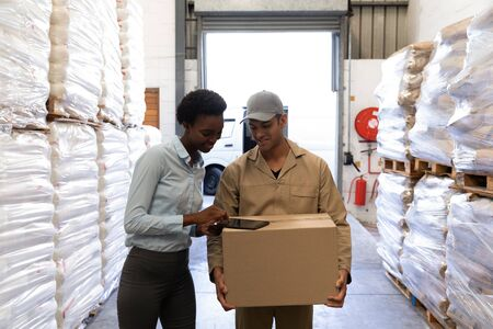 Front view of male worker and female manager discussing over digital tablet in warehouse. This is a freight transportation and distribution warehouse. Industrial and industrial workers concept