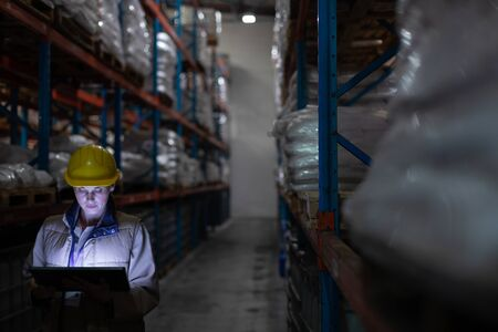 Caucasian female staff using digital tablet in warehouse. This is a freight transportation and distribution warehouse. Industrial and industrial workers concept