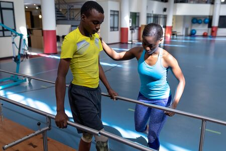 Front view of African-american female physiotherapist assisting disabled African-american man walk with parallel bars in sports center. Sports Rehab Centre with physiotherapists and patients working together towards healing
