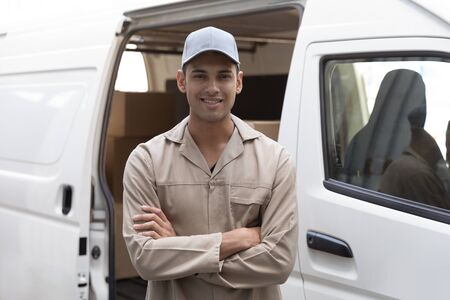 Front view of delivery man standing with arms crossed near van outside the warehouse. This is a freight transportation and distribution warehouse. Industrial and industrial workers concept Archivio Fotografico - 128271031