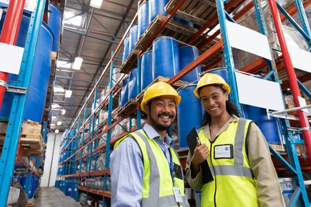Low angle view of happy male and female worker looking at camera in warehouse. This is a freight transportation and distribution warehouse. Industrial and industrial workers concept
